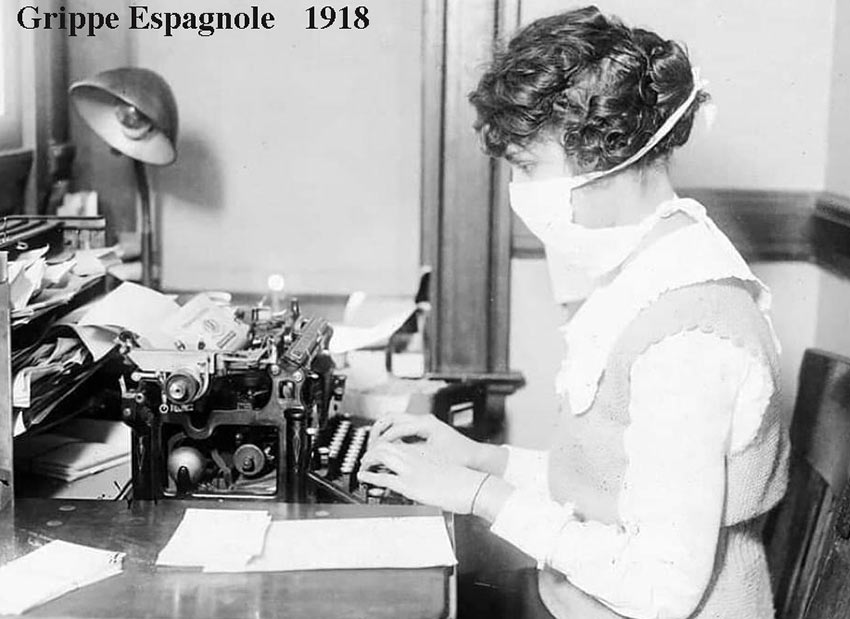 1918-une secrétaire tape à la machine en portant un masque